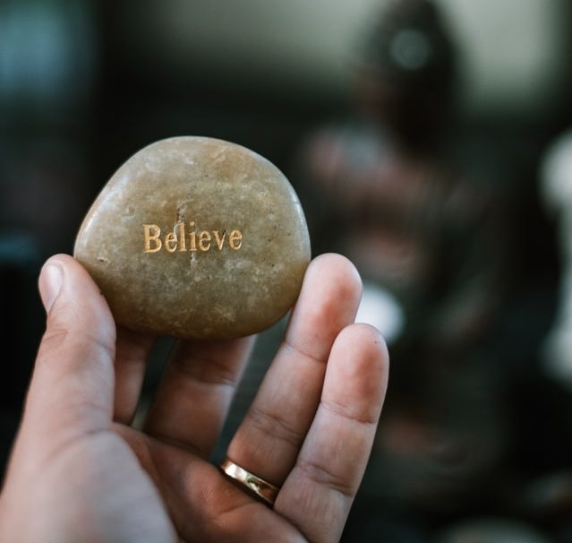 Hand with pebble saying Believe