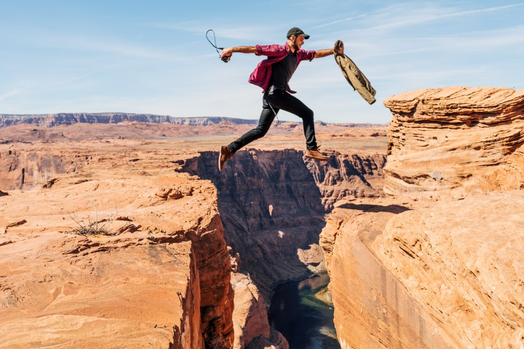 Man jumping over a gap in the canyon. Transform your life.