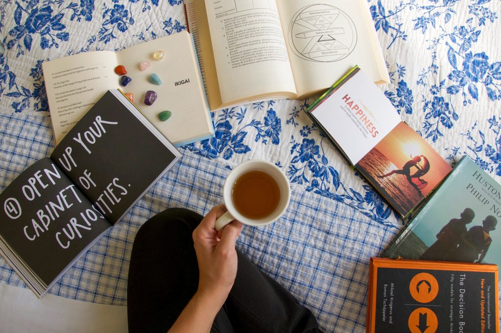 Lady sitting on bed with tea in hand and books to transform your life and expand your mindset
