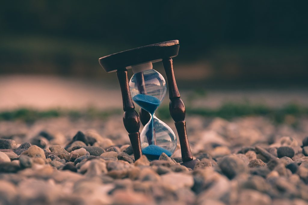 Slanted hourglass surrounded by stones to signify the time it takes to change your destiny
