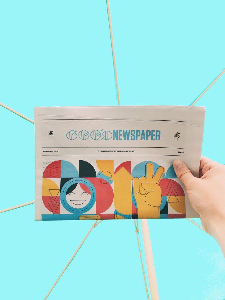 Hand holding up a good news newspaper