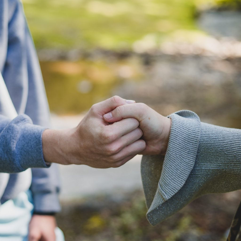 Man and woman interlocking hands giving each other reassurance of their life choices