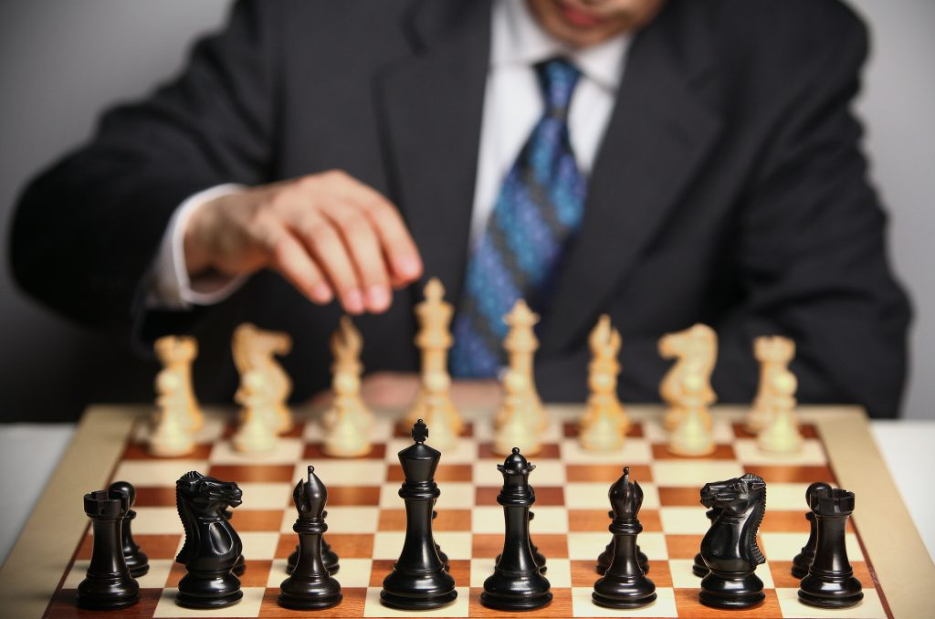 Man playing chess representative of going along with relationships dynamics of a life choice decided for someone