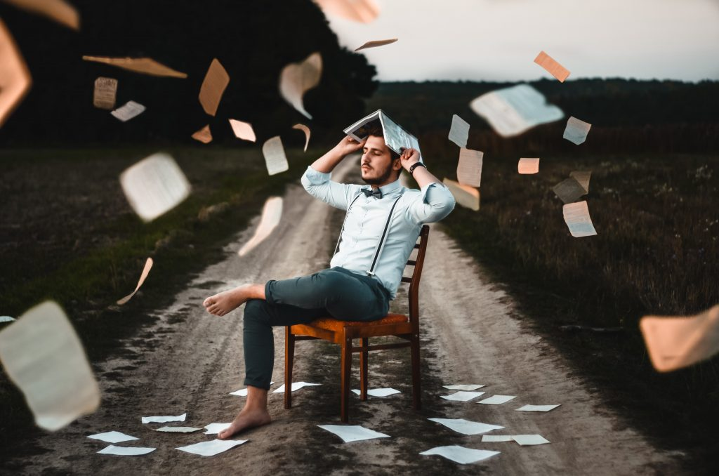 Man sitting on a chair barefoot with pages of books thrown up in the air re-learning how to make himself a priority