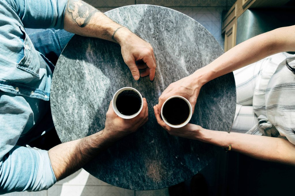 Two people at a table with coffees in hand asserting their wants, needs and desires to make themselves priorities in their lives