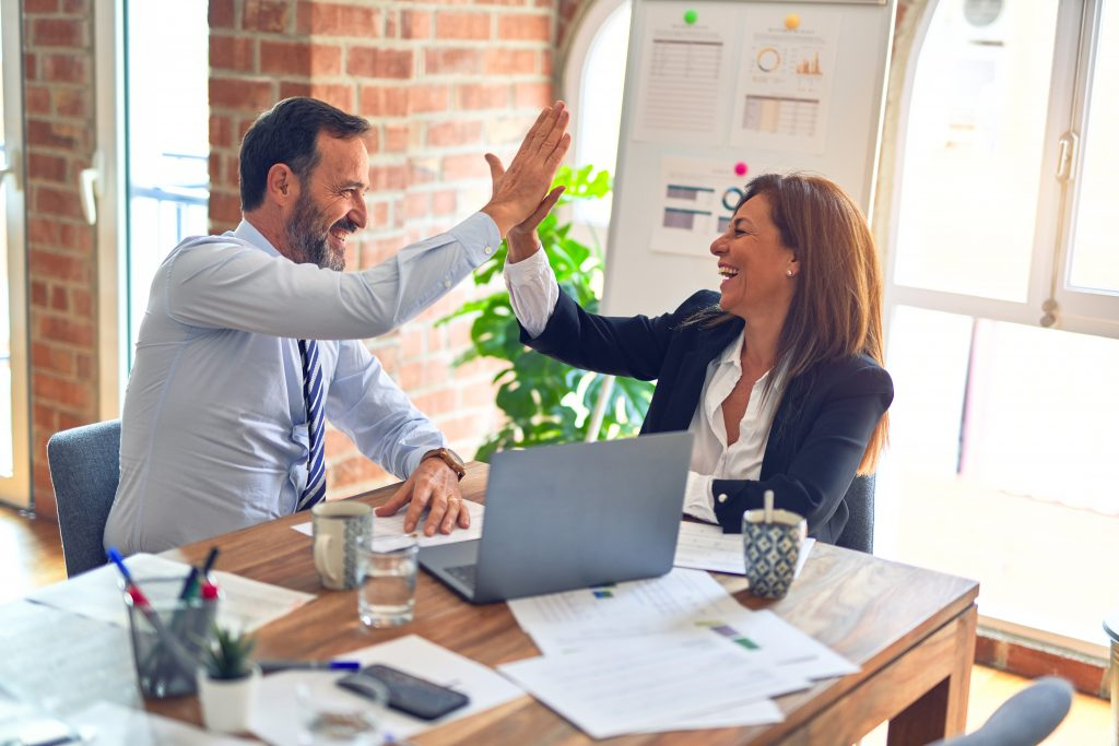 Man and Woman high fiving each other at work celebrating each others life choice