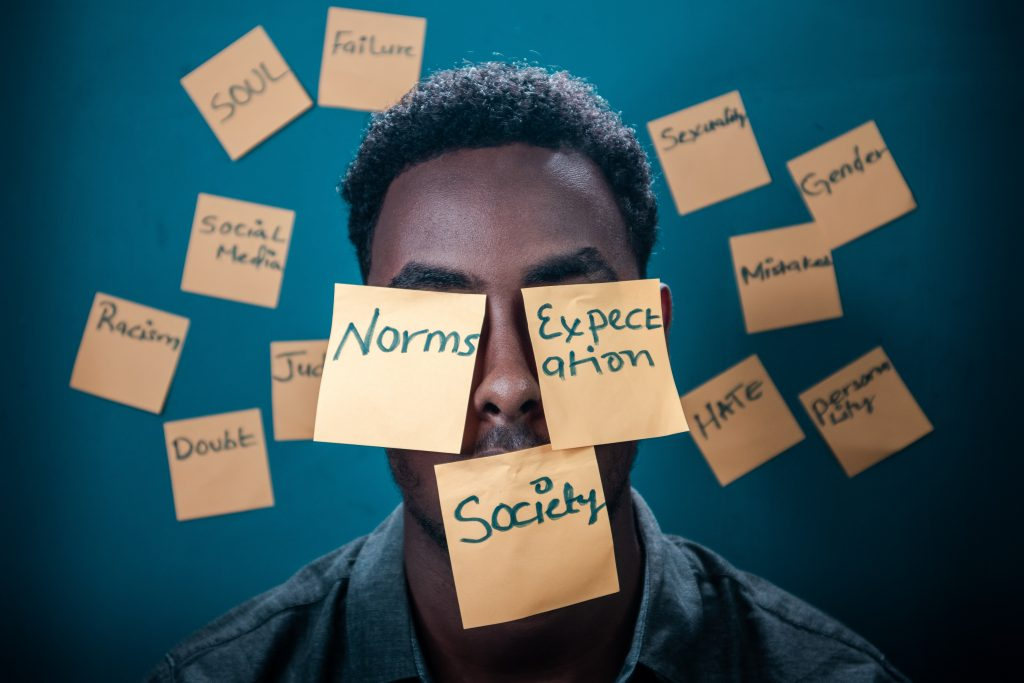 Man with post it notes all over face of different society factors making him doubt himself.