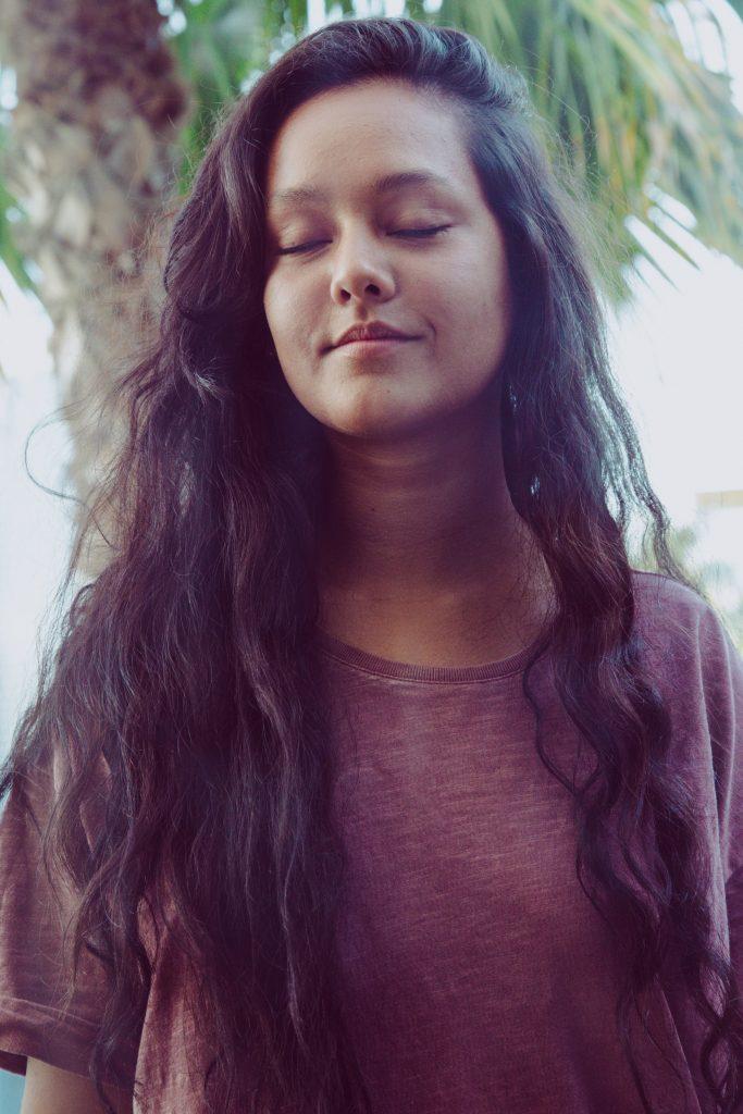 Girl closing her eyes reimagining her past regrets