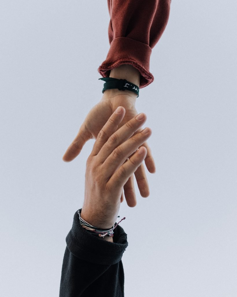 Two people with their hands out to each other supporting one another to leave their jobs