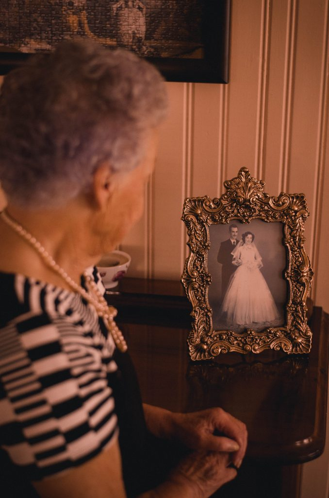 Elderly lady staring at a wedding photo of her and her husband thinking about past regrets