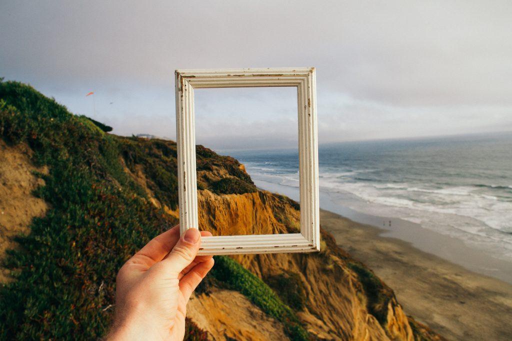 Man on a beach holding up a frame