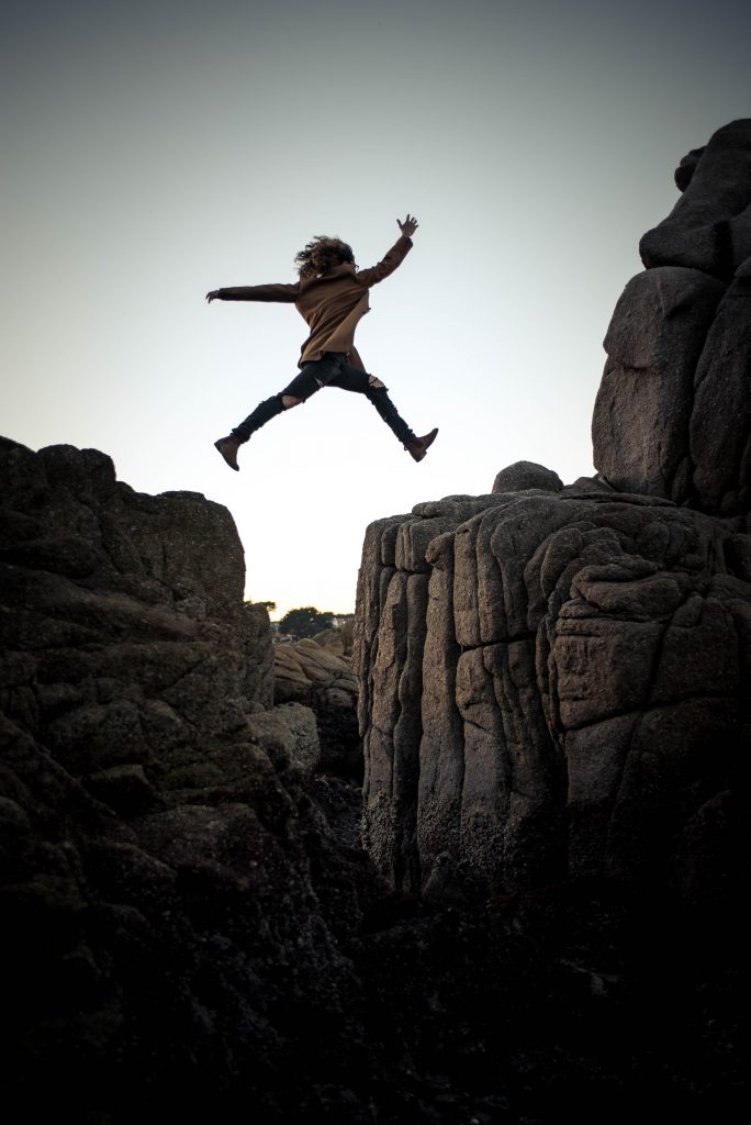 Man taking a leap of faith over rocks to leave his job