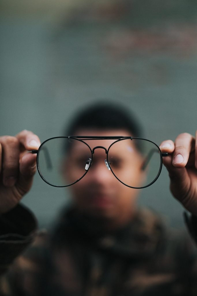 A man blurred out looking through his glasses to show a different perspective a Counselling Psychotherapist can provide following a change of jobs