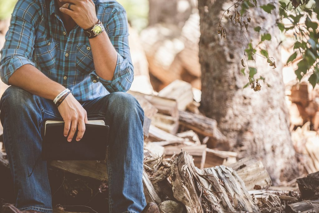 Man sitting on a log with a notebook in hand contemplating how to make life better