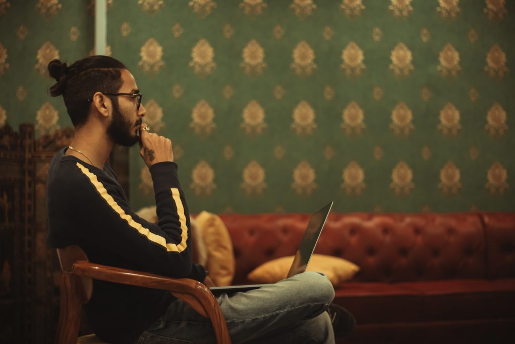 Man sitting on a red couch with his laptop thinking about his life passion