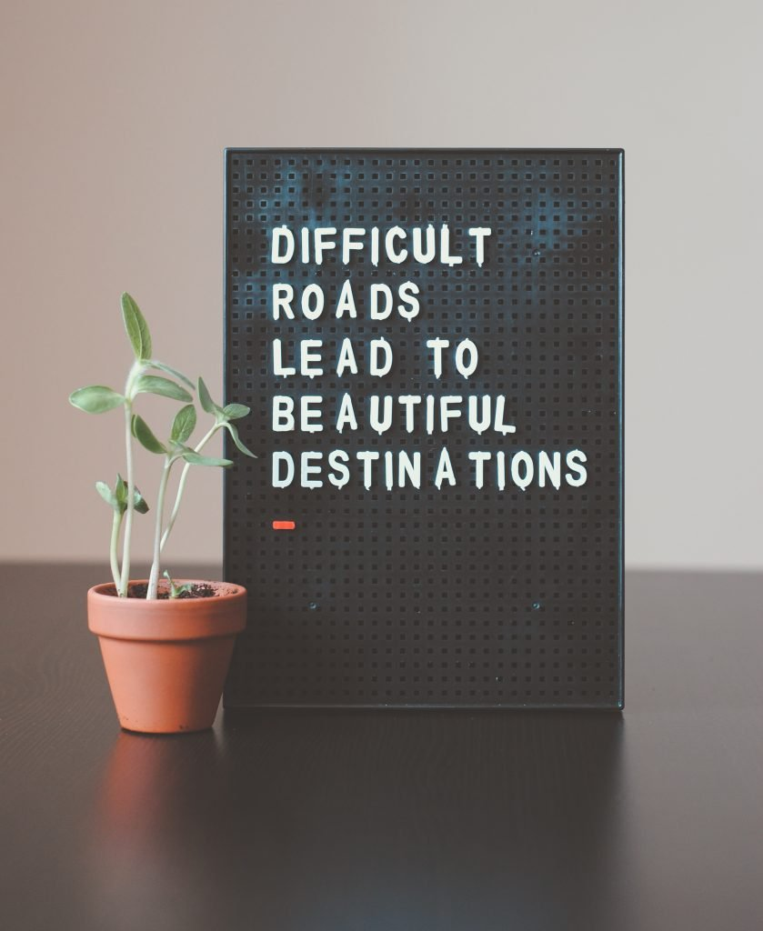 Board next to a plant with the words difficult roads lead to beautiful places, therefore, how therapy helps you to find your life passion