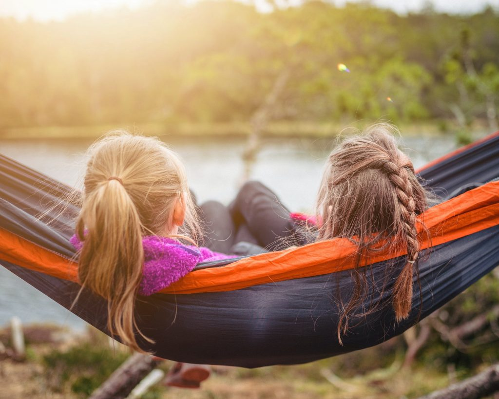 Two girls sitting on a hammock by a lake feeling safe to find the real you