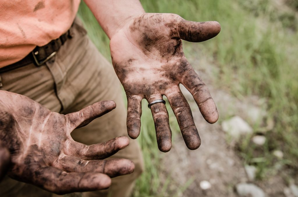 Man with muddy hands to show how you become good at certain things and how these inform your passion career