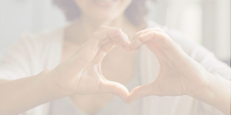 Woman smiling making a heart shaped sign with her fingers