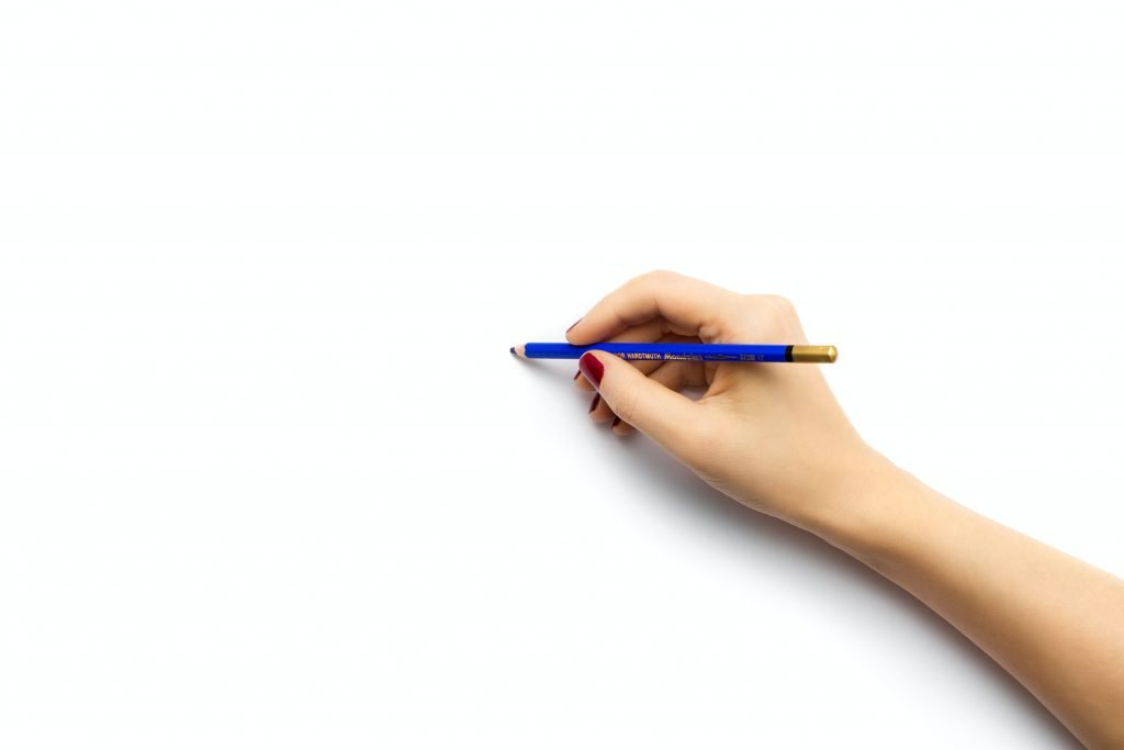 Woman with a pencil in hand writing on a blank page the how to, to figuring out what to talk about in therapy