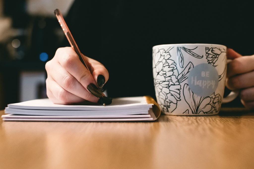 Woman writing in her journal reflecting to find her dream career with a mug that says be happy