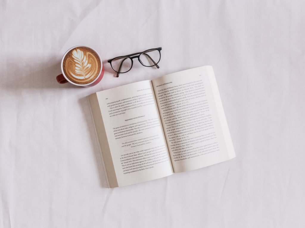 A book with a pair of glasses above and a coffee to find the real you