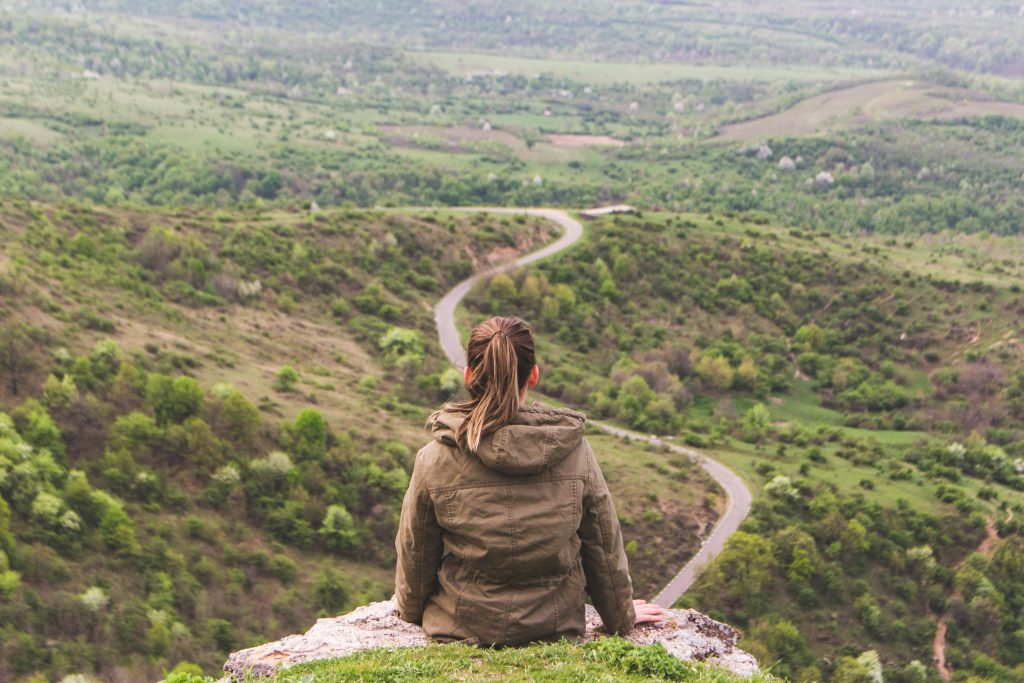 Woman looking down the trail of a mountain to distinguish between her true and false self