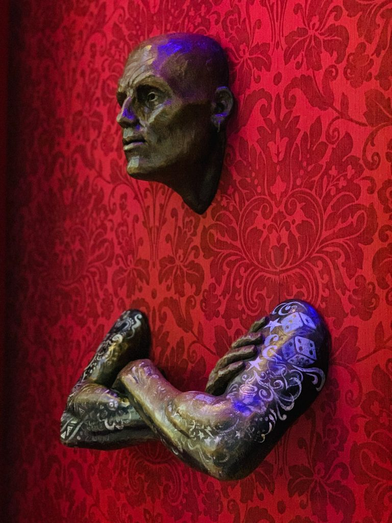Statue stuck in a red patterned wall with only his head and arms showing, therefore, stuck in his emotions and lack of perspective change