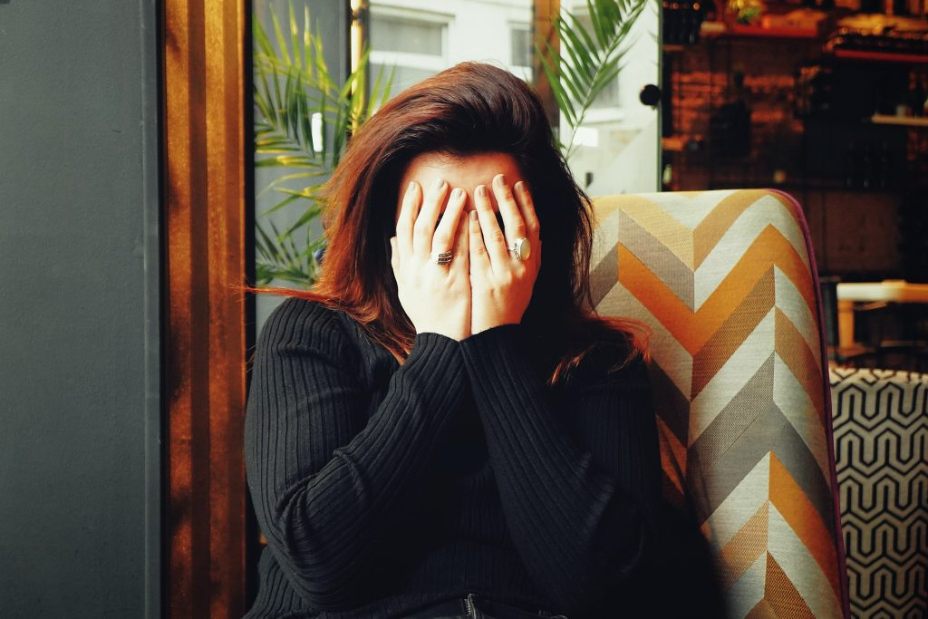 Woman covering her face ashamed and embarrassed at taking action on the notion of working on yourself