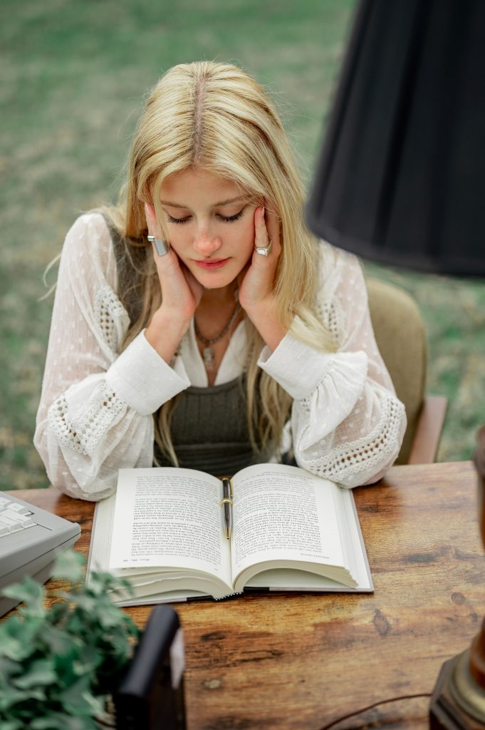 Woman sitting outside on a desk reading thinking her conscious mind alone is enough to answer the question how to change yourself