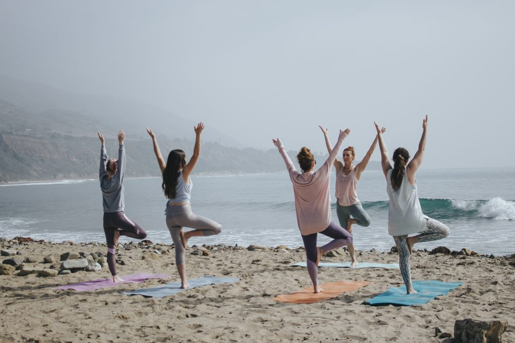 A group of women doing yoga on the beach after figuring out the answer to the question how can I be happy in life