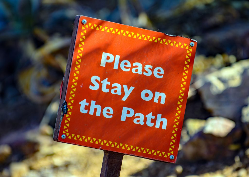 A sign with the words please stay on this path to show what it takes to change and improve yourself
