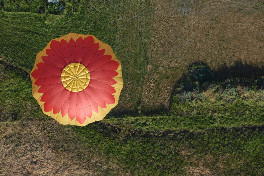 Birdseye view of a hot air balloon in a field to depict getting a change in perspective