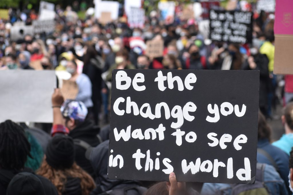 A protesters rally with a board that quotes 'Be the change you want to see in the world' reinforcing the question how to change myself
