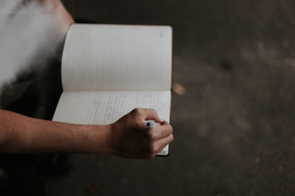 A person with a journal and pen in hand to show new skills to learn