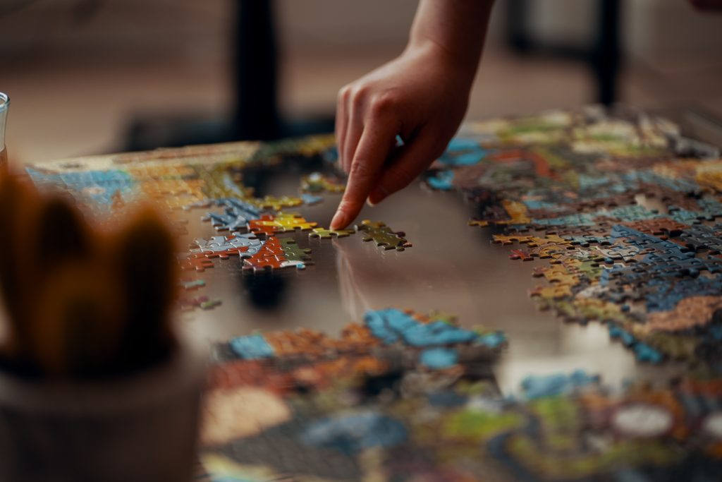 A person putting together a jigsaw puzzle in search of the answer how to find my passion