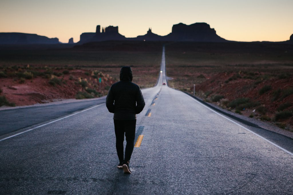 Man looking at a long stretch of road answering the question 'How to change myself?'