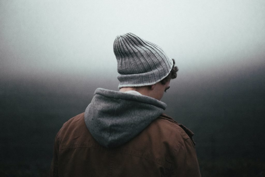 Man with his head slightly down, wearing a grey hat, a hoodie and a brown jacket with his back toward the camera and a shaded black background because he feels unworthy as a result of struggling to find more friends.