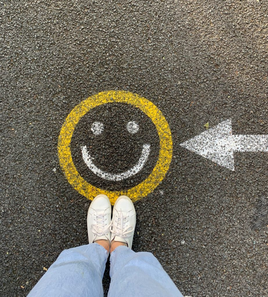 Woman's legs and feet, standing slightly on a smiley face on the ground with an arrow pointing to it showing how to make more friends