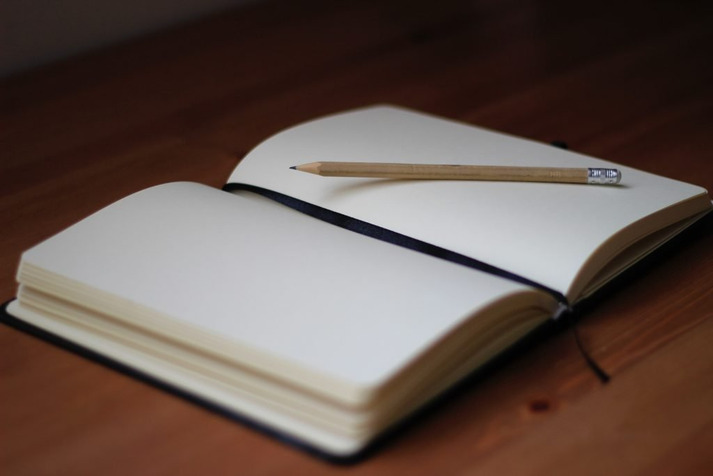 An open, blank page journal with a pencil inside for you to journal the reasons why you want to make more friends