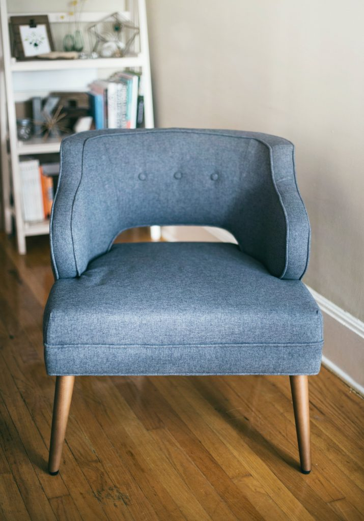 A blue arm chair with a white shelf in the background to show working with a Counselling Psychotherapist if you have no friends