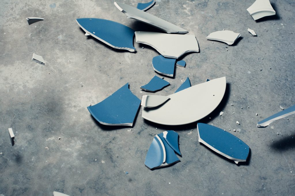 A blue terracota plate smashed on the floor to show therapy doesn't make you weak as it forces you to dismantle your beliefs