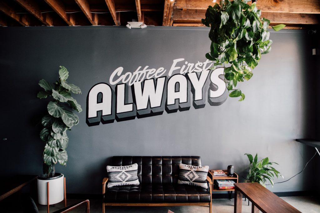 A grey wall with the words coffee first always. Therefore, how you need to treat therapy too