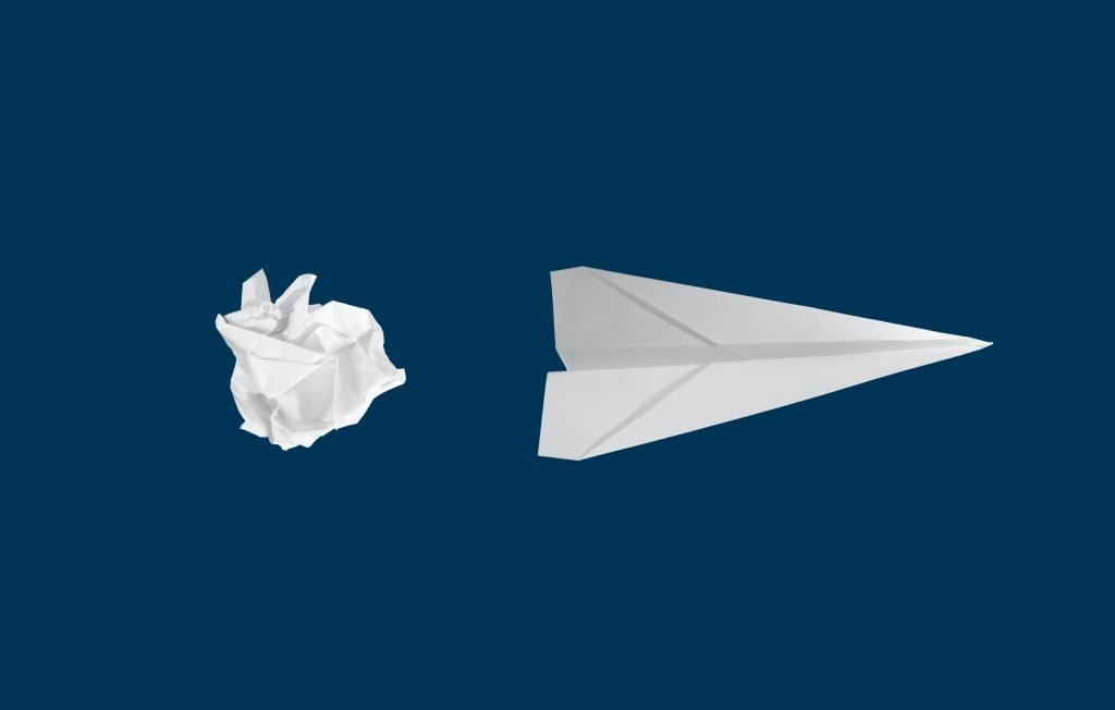 A paper scrunched up in a ball next to a paper aeroplane to signify the direction to go in to figure out the answer to 'How do I know what I want to do?'