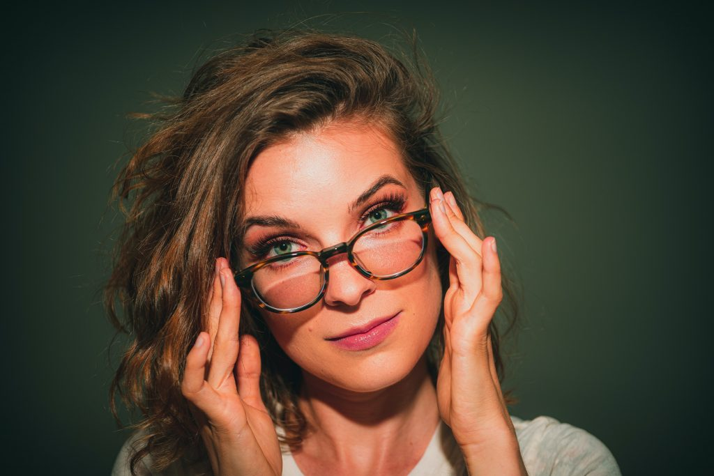 A woman tilting her head, whilst touching her glasses to indicate being smart as a result of working with therapist, not weak