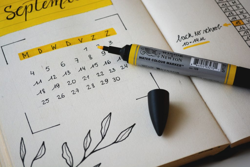 A marker pen and a calendar to show the importance of planning in getting the energy to clean your house