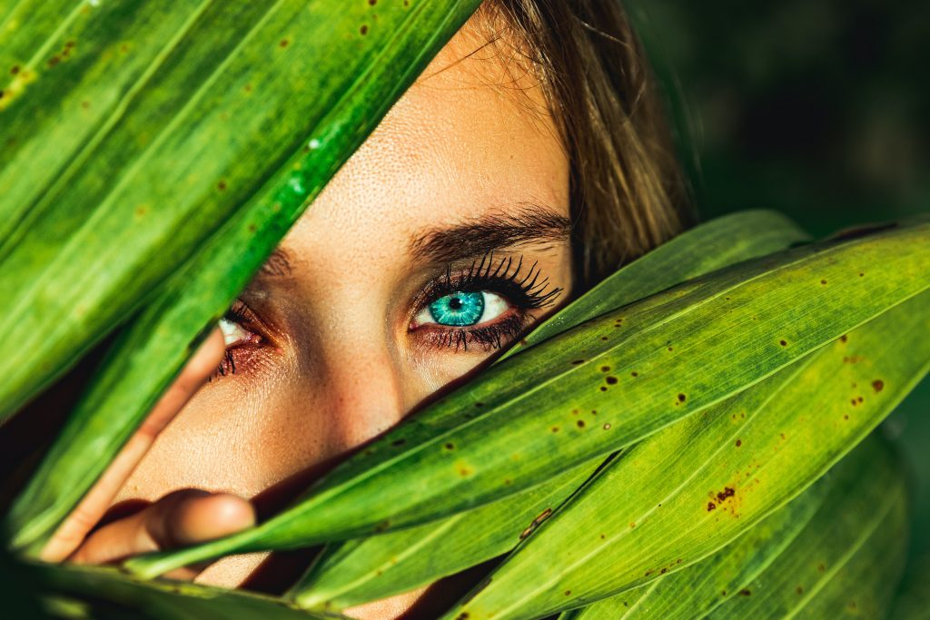 Woman hiding behind plant leaves to understand what happens when you run away from your problems