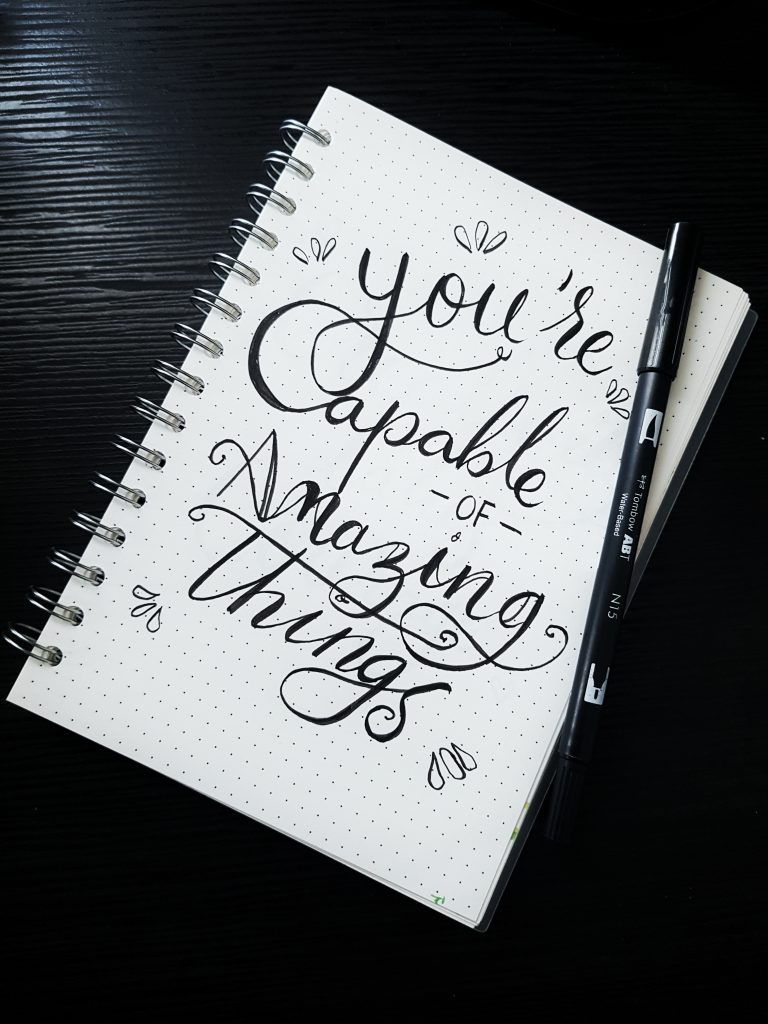 A notebook with the phrase you're capable of amazing things. So learn to stop mindlessly scrolling.