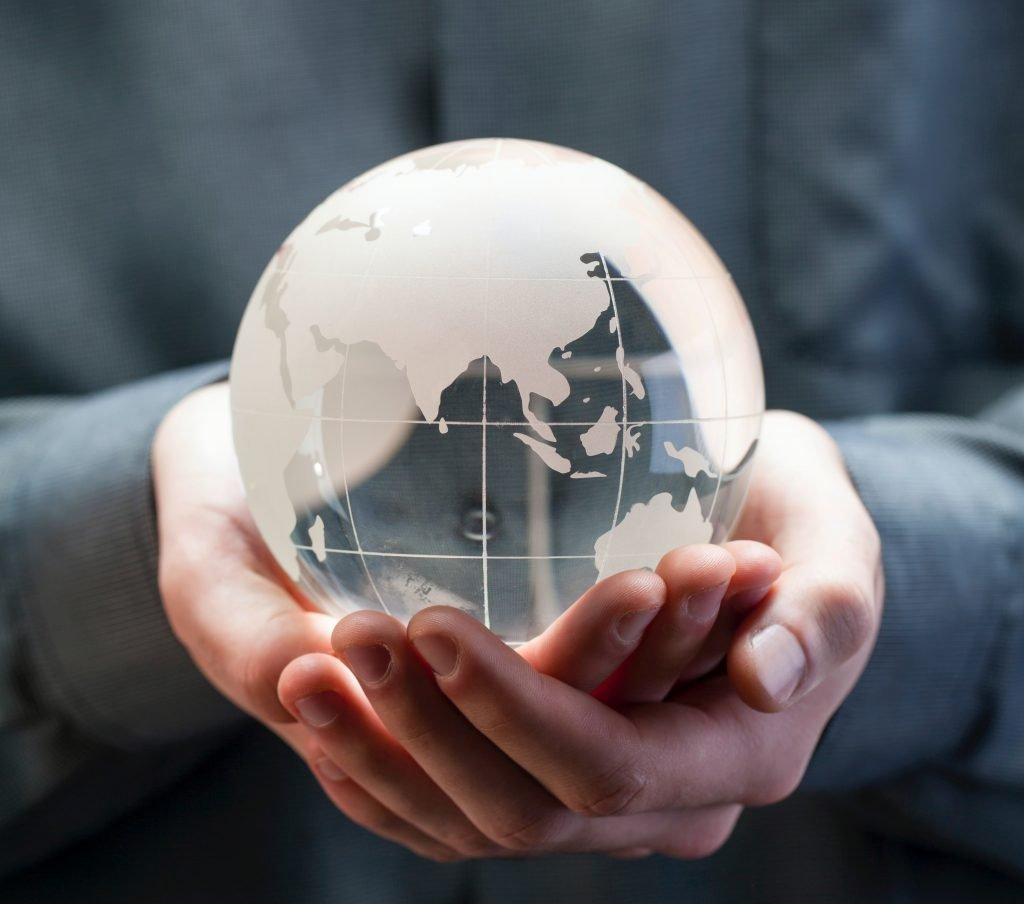 A person holding a glass world ornament in their hand to show the benefits of learning how to deal with crushing failure at work.