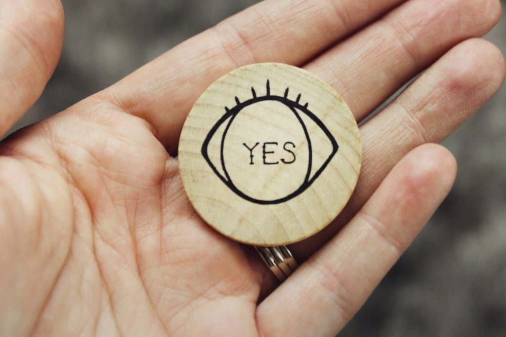 Man holding a token with an eye drawn on it and the words yes inside to affirm how to deal with crushing failure.